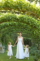Two young girls and mid adult bride under ivy arches holding hands portrait (thumbnail)