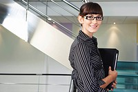 Young businesswoman standing in office corridor smiling portrait