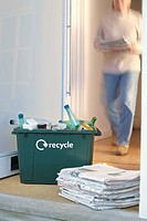 Recycling container and pile of waste paper on floor woman walking in background motion blur