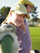 Two young golfers on court focus on woman (thumbnail)