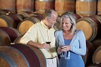 Man and woman with wine_glass aside wine casks