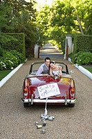 Portrait of newlyweds in vintage convertible