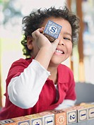 Boy playing with alphabet blocks portrait