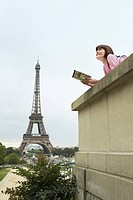France Paris Young woman reading book on balcony in front of Eiffel Tower