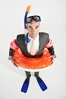Middle_aged businessman in flippers inflatable rubber ring snorkel and goggles