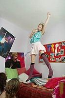 Girl jumping on bed singing friends watching from floor (thumbnail)