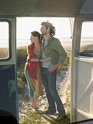 Young couple embracing view through open door of camper van (thumbnail)