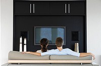 Couple sitting in front of flat screen television in living room back view (thumbnail)