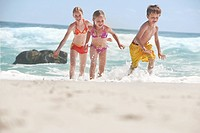 Three children 5_6 7_9 10_12 running on beach