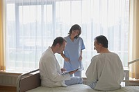 Doctor and Nurse Consulting with Patient in hospital room