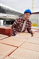 Young construction worker leaning on tiles