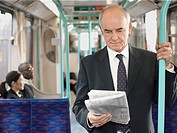 Businessman Reading Newspaper on Train holding onto bar