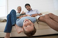 Boy hanging upside down off couch with father and grandfather sitting beside him