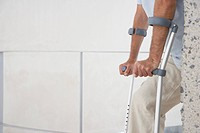 Mid_adult man on crutches mid section side view