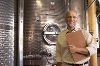 Portrait of winemaker standing next to wine vat holding clipboard