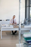 Businessman sitting at desk in office working (thumbnail)