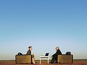 Business people sitting in chairs on open plain