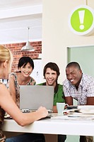 Four people having meeting around laptop laughing