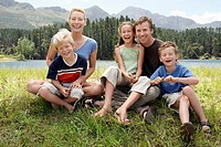 Three children 7_9 sitting outdoors on grass with parents family portrait