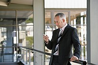 Businessman leaning on railing using mobile phone