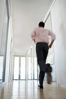 Businessman Running in Corridor low angle back view