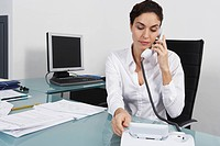 Businesswoman dialling telephone in office