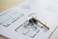 Key ring with three keys lying on architectural blueprint close_up