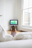 Girl 5_6 watching cartoons in television back view