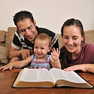 A young Christian family reading the Bible together