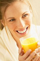 Close_up of a young woman drinking orange juice