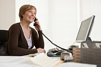 Middle_aged woman at computer talking on telephone