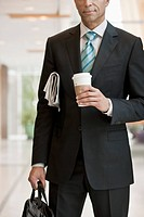 Businessman with a paper, a briefcase and a cup of coffee