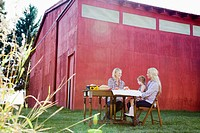 Women and young girl eating beside a barn