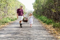 Little girl and woman carrying a basket of fresh food down a country lane