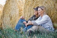 Middle aged couple relaxing beside fresh hay rolls