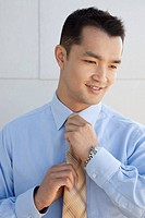 Young man adjusting his necktie