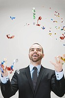 Young businessman throwing confetti