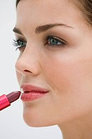 Fashion model applying lipstick on her lips (thumbnail)