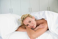 Close_up of a woman lying on the bed and smiling