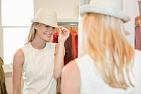 Woman trying on a fedora in a boutique and smiling