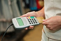 Mid section view of a woman using a credit card reader in a boutique
