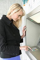 Woman entering pin number in an ATM