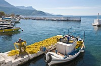 A fisherman mending nets on the quay side in the little harbour at Ayios Nikolaos, in The Outer Mani, Southern Peloponnese, Greece