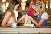 Two women holding shopping bag in a cafe