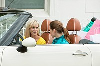 Two women smiling in a car after shopping
