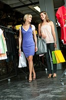 Female friends carrying shopping bags in a boutique