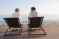 Couple sitting on deck chairs on the beach