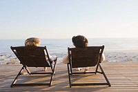 Couple reclining on deck chairs on the beach