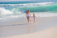 Woman running on the beach with her daughter