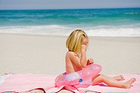 Girl sitting with an inflatable ring on the beach and crying